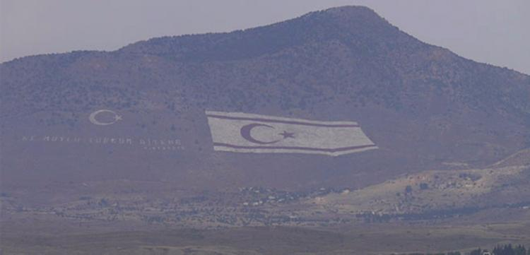 """Kürdistan dağlarına çizdiği devasa bayraklarla işgalini """"inandırıcı"""" kılmaya çalışmasıyla tanıdığımız Türk devlet mantığı, Kıbrıs'ta da huyundan vazgeçmiyor elbette. Fotoğrafta görülen Beşparmak Dağları üzerindeki bayrak ve """"Ne mutlu Türk'üm diyene"""" yazısı, Kıbrıslı Rumların her gün işe giderken görebileceği biçimde kurgulanmış... İşgalcinin 'aşağılık kompleksi' öyle güçlü ki üstelik, bayrakların dibindeki köyde elektrikler kesilse bile bayrağı aydınlatan ışık hiç sönmüyor!"""